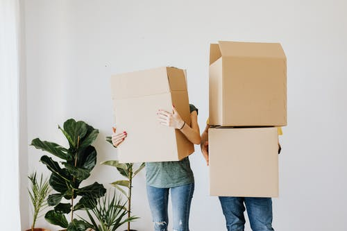 Unrecognizable couple wearing jeans standing carrying stacked carton boxes out of apartment during renovation on daytime